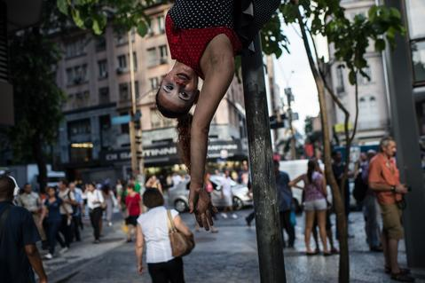 "A performer hangs from a post during the ""Anjos do Picadeiro"" annual week-long event in Rio de Janeiro, Brazil, on December 5, 2013. About 100 clowns and street performers turn a street into a theater until December 7."