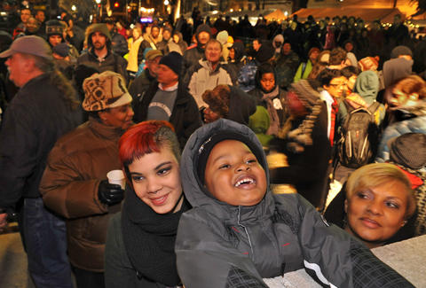 Deandre Fraling, 4, of Baltimore, center, got into the holiday spirit with his grandmother, Tanya Paris, at right in front, and their friend, Kiana Belton, at the 41st annual lighting of the Washington Monument.