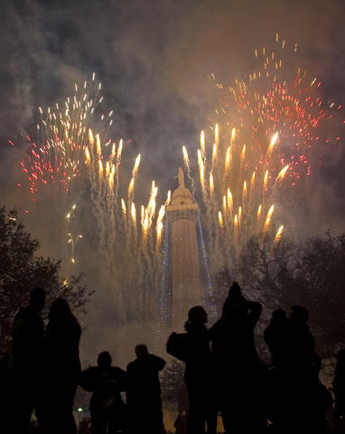 People are silhouetted as fireworks dance around Baltimore's Washington Monument in a view from the east.