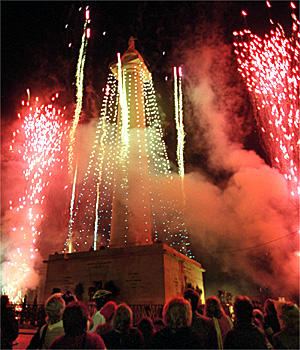 Spectators watch as fireworks burst over Mount Vernon during the annual holiday lighting of the Washington Monument. About 7:30 p.m. yesterday, Mayor Martin O'Malley flipped a switch that turned on nearly 1,000 bulbs in 28 vertical strands of blue and white as 1,000 pounds of fireworks boomed overhead and embers cascaded down the 178-foot-tall monument.
