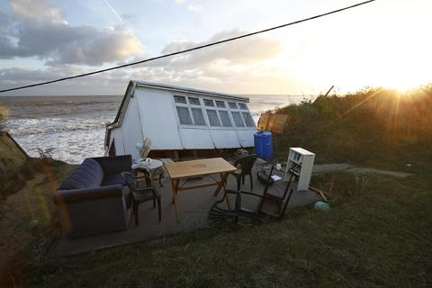 Furniture sits in the garden of a house that fell into the sea during a storm surge in Hemsby, eastern England December 6, 2013.