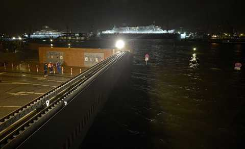 "A giant tide gate is closed at flooded famous landmark ""Fischmarkt"" (Fish Market) in the early morning hours in the harbour of Hamburg, December 6, 2013. Hurricane-force storm Xaver blasted towards mainland Europe on Friday after cutting transport and power in northern Britain and killing three people in what meteorologists warned could be the worst storm to hit the continent in years."