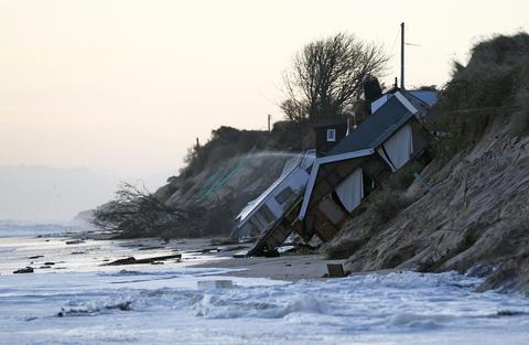 Collapsed houses lie on the beach after a storm surge in Hemsby, eastern England December 6, 2013.
