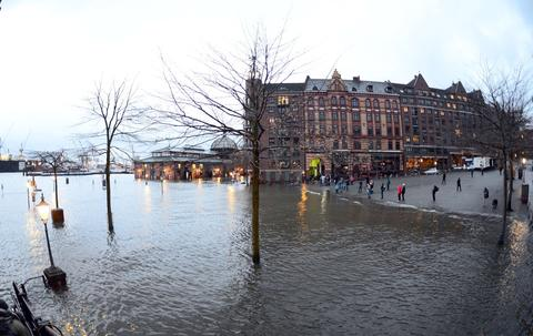 People look at the water level of the Elbe river near historic fish auction hall Fischmarkt remained flooded on December 06, 2013 after the storm Xaver reached the northern German city of Hamburg during the night. A fierce storm battered northern Europe with hurricane force winds leaving five people dead or missing, disrupting travel and forcing thousands to flee their homes over fears of the worst tidal surge in decades.