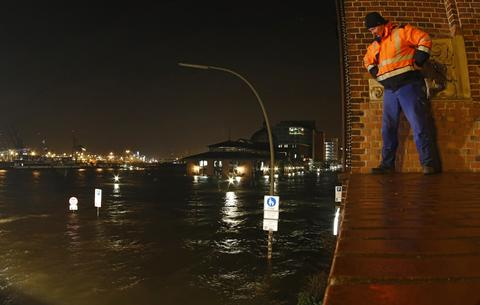 "HAMBURG, GERMANY - DECEMBER 6: Workers observe the flooded waterfront at the ""Fischmarkt"" (fish market) on December 6, 2013 in Hamburg, Germany. Germany is assessing the damage caused by ""Xaver,"" one of the most severe storms to hit the region in decades."