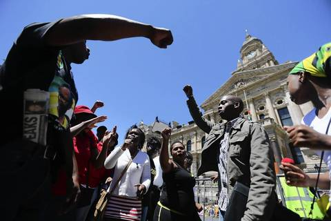 South African mourners sing and dance in front of the Cape Town City Hall where the late South African president Nelson Mandela made his first public address after being released in Cape Town, South Africa.