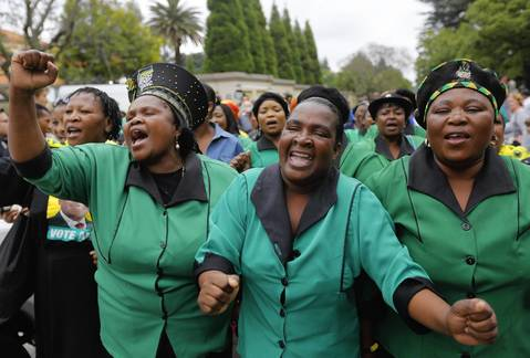 Mourners sing songs outside the house of the late South African president Nelson Mandela in Johannesburg, South Africa.