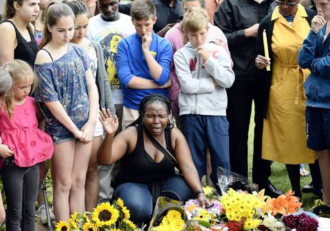 A woman, surrounded by other people who pay their respects, prays outside the house of former South African President Nelson Mandela in Johannesburg