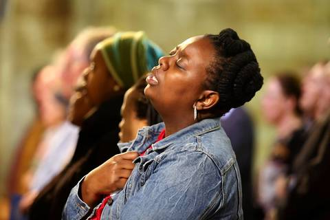 A mourner sings the South African National anthem and hymn Nkosi Sikelel' iafrica during a mass at St Georges Cathedral in Capetown following the death of former South African President Nelson Mandela.
