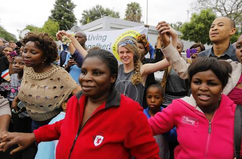 Mourners gather and pray and sing outside the house of the late South African president Nelson Mandela in Johannesburg, South Africa.