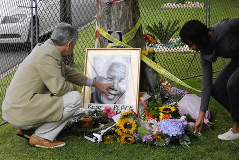 A mourner touches a photograph of late South African president Nelson Mandela placed outside Mandela's house in Johannesburg, South Africa.