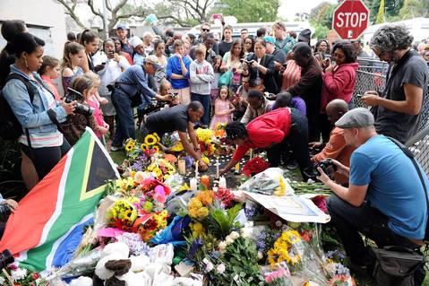 People light candles on December 6, 2013 outside the house of former South African President Nelson Mandela in Johannesburg.