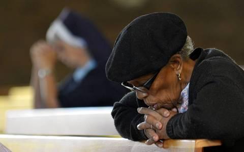 A woman prays for South African president Nelson Mandela at Regina Mundi Church in Soweto.