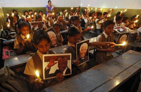 Schoolchildren hold candles and portraits of former South African President Nelson Mandela during a prayer ceremony at a school in the western Indian city of Ahmedabad.
