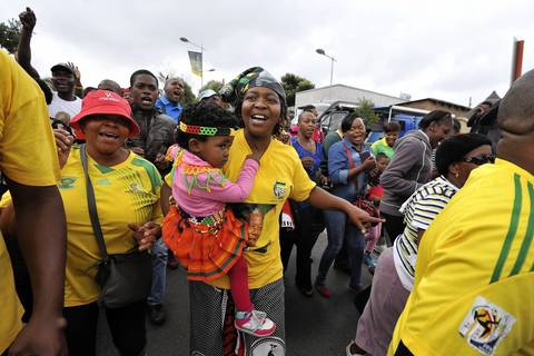 People sing and dance during a gathering of mourners on Vilakazi Street in Soweto, where the former South African President Nelson Mandela resided when he lived in the township.