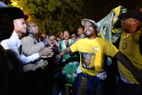 People sing and dance during an all night vigil outside the home of former.South African President Nelson Mandela in Johannesburg