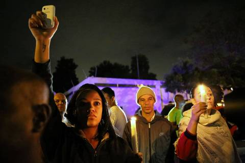 South Africans hold a candlelight vigil outside the house of former South African President Nelson Mandela following his death in Johannesburg on Dec. 5, 2013