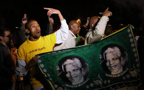 South Africans hold pictures of former South African President Nelson Mandela as they pay tribute to him following his death in Johannesburg on Dec. 5, 2013
