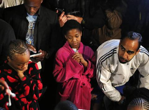 People listen to a radio as South African President Jacob Zuma announces the death of former South African President Nelson Mandela in Houghton Estate, a suburb of Johannesburg, on December 5, 2013. Mandela died peacefully at his home on Thursday after a prolonged lung infection, Zuma said.