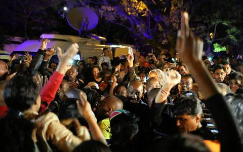 South Africans react as they pay tribute to former South African President Nelson Mandela following his death in Johannesburg on December 5, 2013.
