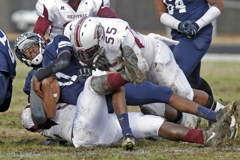 Heritage's Ian Giddings, left, and Darrion Turner, right, tackle Dinwiddie quarterback Ronald Kearney, center, during Saturday's Group 4A state semifinal game at Dinwiddie Middle School.
