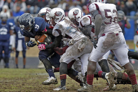 Dinwiddie's Rashard Hicks, left, runs through the defense of Heritage during Saturday's Group 4A state semifinal game at Dinwiddie Middle School.