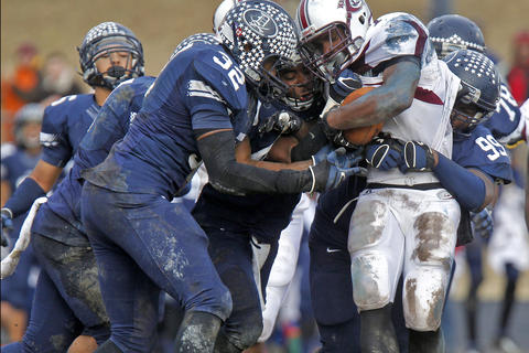 Heritage's Juany'e Patillo, right, is brought down by Dinwiddie defenders during Saturday's Group 4A state semifinal game at Dinwiddie Middle School.