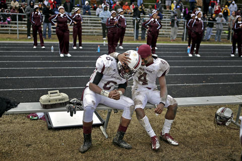 Heritage's Marcus Vanhook, right, comforts Demarea Pickens on the sidelines late in the fourth quarter during Saturday's Group 4A state semifinal game against Dinwiddie.