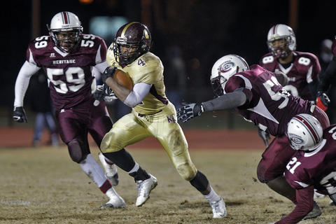Kings Fork running back Deshaun Wethington, center, cuts through the Heritage defense during Friday's 4A South semifinal game at Todd Stadium.