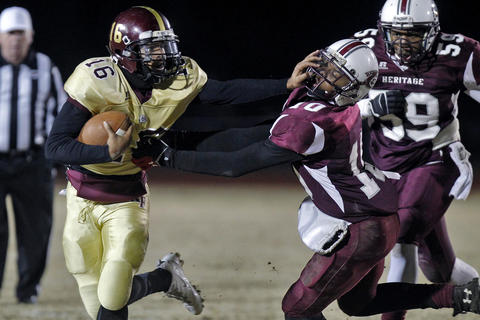 Kings Fork quarterback Uriah Adams, left gives a stiff arm to Heritage's Justice Faulteroy during Friday's 4A South semifinal game at Todd Stadium.