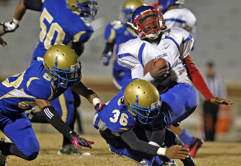 Phoebus' Deshawn Pope, center, tackles Caroline's Rayquan Smithers, right, during Friday's game at Darling Stadium.