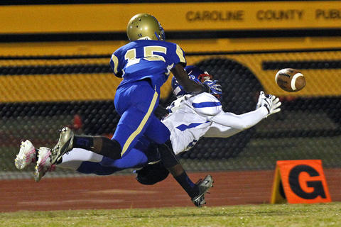 Caroline's Keyshwan Johnson, right, misses catching the ball with pressure from Phoebus' Darius Jones, left, during Friday's game at Darling Stadium.