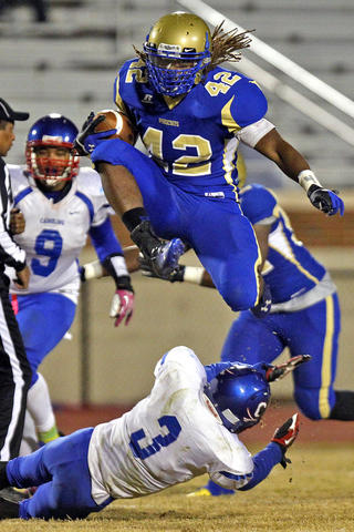 Phoebus' Marshwan Williams hurdles Caroline's Jaquan Monroe on his way to a touchdown during Friday's game at Darling Stadium.