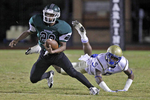 Kecoughtan's Victor Mitchell, left, avoids the tackle of Phoebus' Antonio Brown, right, during Friday's game at Darling Stadium.