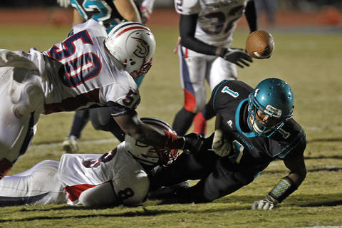 Woodside's Jay'Quan Lassiter, right, fumbles the ball while being tackled by Denbigh's Rashaad Pressey, top, and Patrick Smith, bottom, during Thursday's game at Todd Stadium.