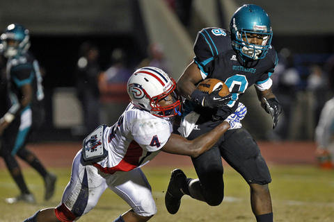 Denbigh's Derek Melton, left, attempts to tackle Woodside's Darius Howell during Thursday's game at Todd Stadium.