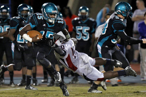Woodside's L.J. Taylor, left, dodges the tackle of Denbigh's Rashaad Pressey during Thursday's game at Todd Stadium.