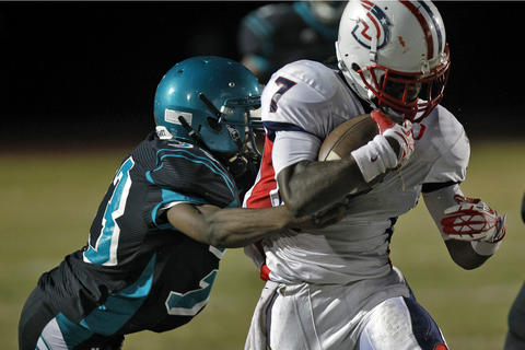 Denbigh's Darius Banks, right, is tackled by Woodside's Isaiah Moore during Thursday's game at Todd Stadium.