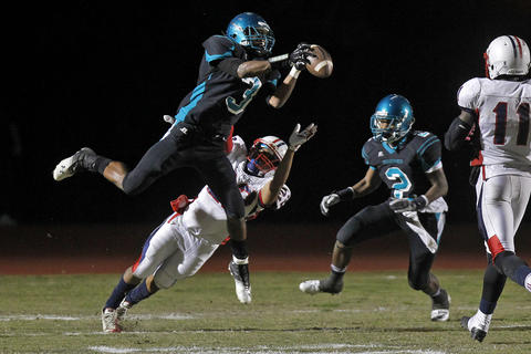 Woodside's Trey Reed, left, intercepts a ball intended for Denbigh's Larico Robinson in the first half during Thursday's game at Todd Stadium.