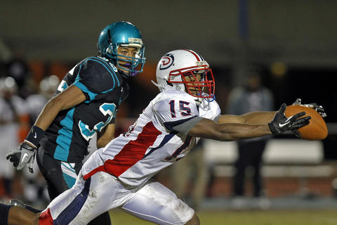 Denbigh's Kalihl Wharton catches the ball around Woodside's Devon Thomas, left, during Thursday's game at Todd Stadium.