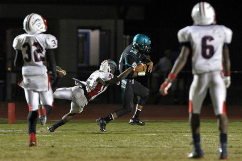 Woodside's Ray Jackson heads for the end zone for the game winning touchdown while dragging Denbigh's Derek Melton during Thursday's game at Todd Stadium.