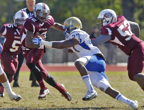 Phoebus' Tyree Steward, center, attempts to tackle Heritage quarterback Jeremiah Boyd during Saturday's game at Todd Stadium.