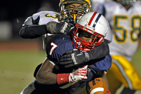 Denbigh's Darius Banks is tackled hard by Bethel's Evan Scott during Friday's game at Todd Stadium.