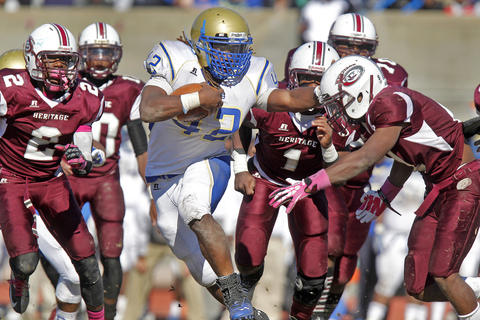 Phoebus' Marshawn Williams, center, gives a stiff arm to Heritage's Marcus Vanhook as he runs away from the defense during Saturday's game at Todd Stadium.