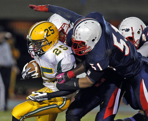 Denbigh's Patrick Prosser, right, dives to tackle Bethel's Dionte Franklin during Friday's game at Todd Stadium.