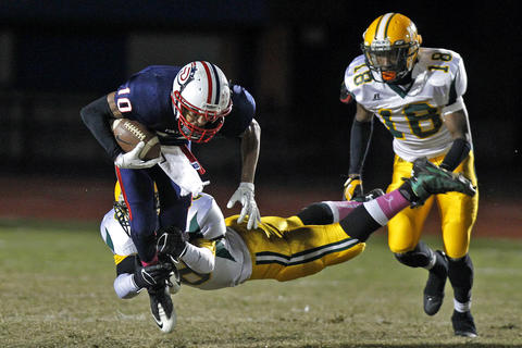 Denbigh's Tyrik Burns, left, is tackled by Bethel's Erick Lyons, center, during Friday's game at Todd Stadium.