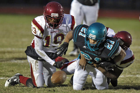 Woodside's Sam Alvarez, center, fumbles the ball while being tackled by Warwick's Rambert Tyree, left, and Devin Simpson, right, during Thursday's game at Todd Stadium.