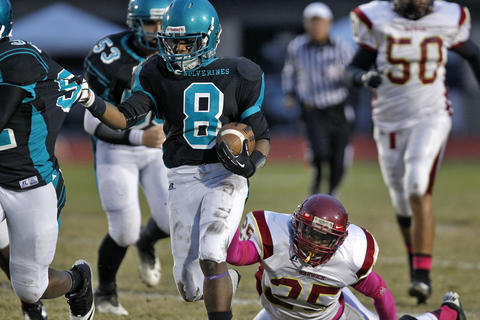 Woodside's Darius Howell, center, runs away from the tackle of Warwick's Tredrick Booze, right, during Thursday's game at Todd Stadium.