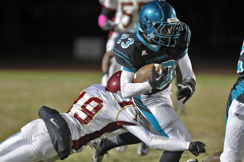 Warwick's Rambert Tyree, left, dives to tackle Woodside's Tamir Walker during Thursday's game at Todd Stadium.