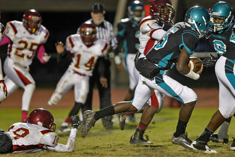 Woodside's L.J. Taylor, right, escapes the tackle of Warwick's Rambert Tyree, left, to run for a touchdown during Thursday's game at Todd Stadium.